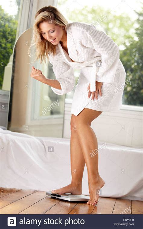 Young girl weighing herself on scales Stock Photo